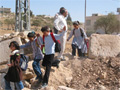 Palestinian schoolchildren cross a roadblock
